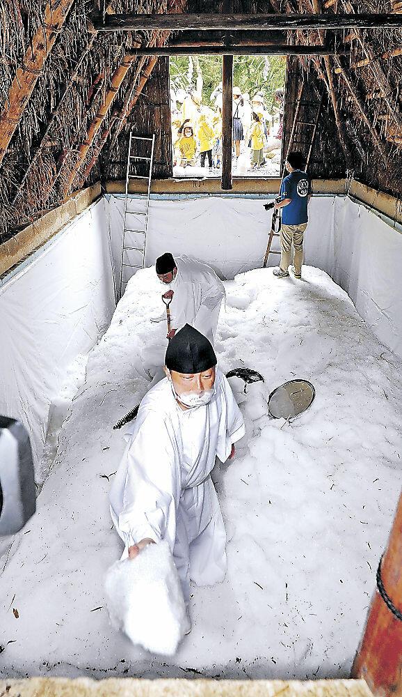 氷室小屋から雪氷を取り出す白装束姿の湯涌温泉観光協会員=金沢市湯涌町