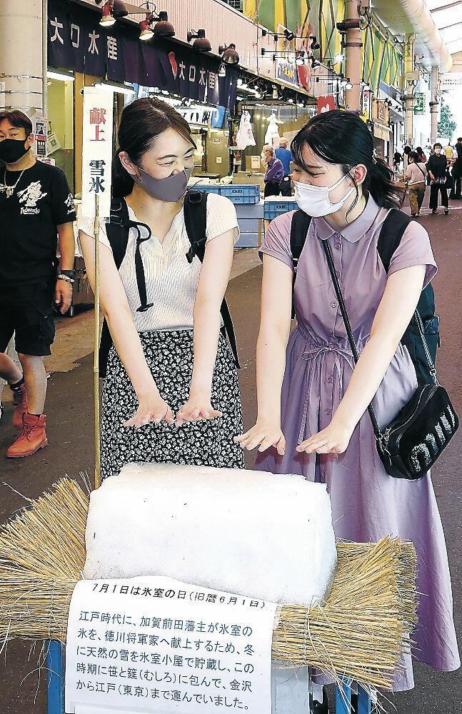 雪氷に手を近づける客=金沢市近江町市場