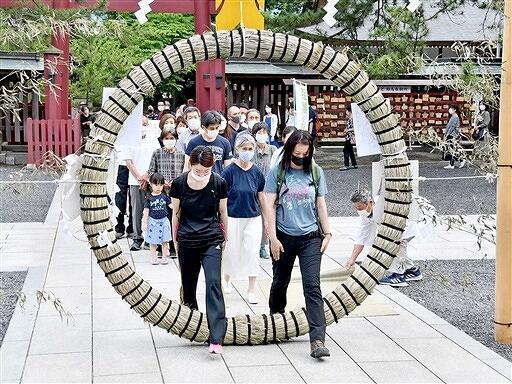 茅の輪をくぐり、罪やけがれを落とす参拝者=6月30日、福井県敦賀市の気比神宮