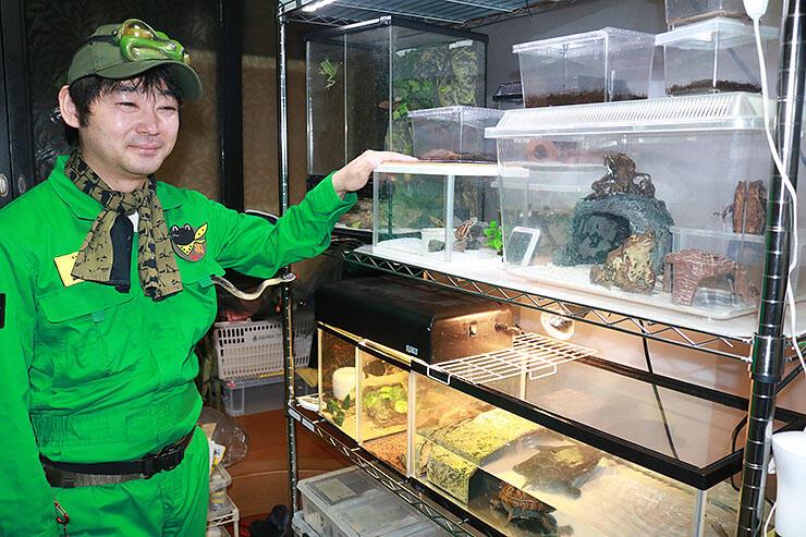 カエルやトカゲなどを飼育する自宅で、緑のつなぎに身を包む高地さん