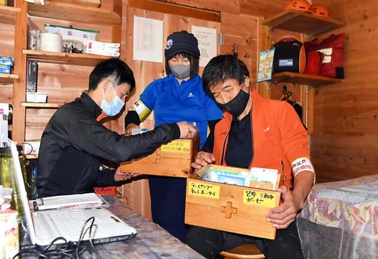 自炊室を改装した「診療所」で備品を確認する師田さん(右)ら