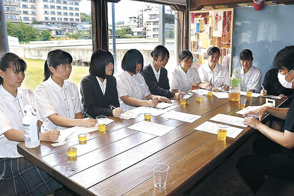 森本理事長(右)から温泉街の状況を聞く生徒=加賀市の湯の元公園