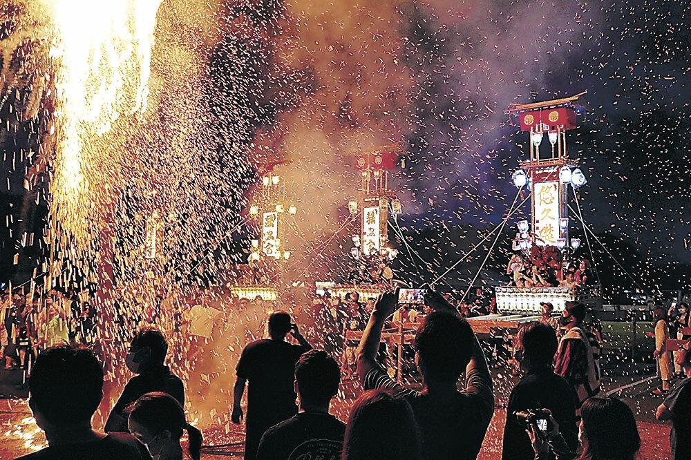 キリコが並んだ前で火がともされた松明=能登町の宇出津港いやさか広場