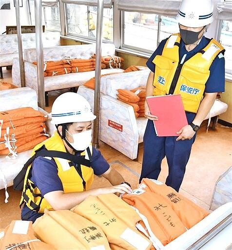 救命胴衣の数を確認する敦賀海上保安部の職員=7月7日、福井県敦賀市蓬莱町
