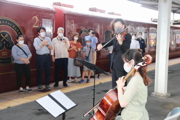 上田駅のホームでバイオリンを演奏する大迫さん(手前から2人目)