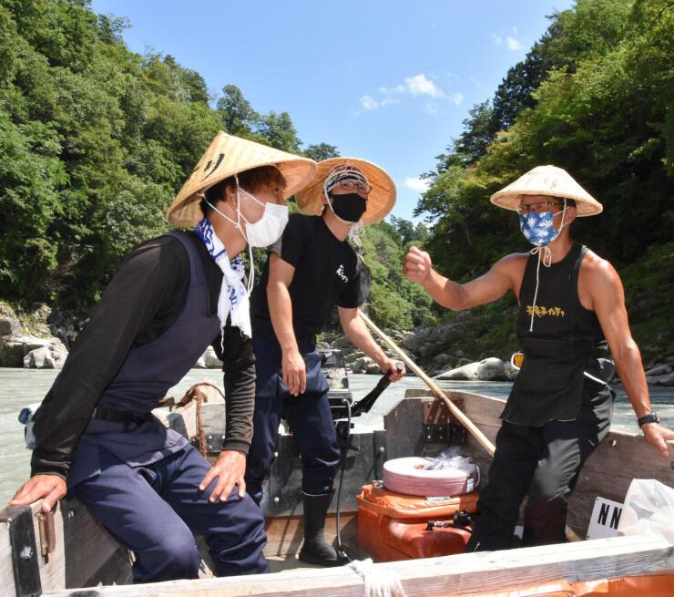 天龍ライン遊舟の船頭(右)から操縦のこつを教わる信南交通の若手船頭ら