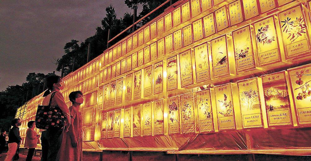 柔らかな光に囲まれ、戦没者の冥福を祈る参拝者=金沢市の石川護國神社