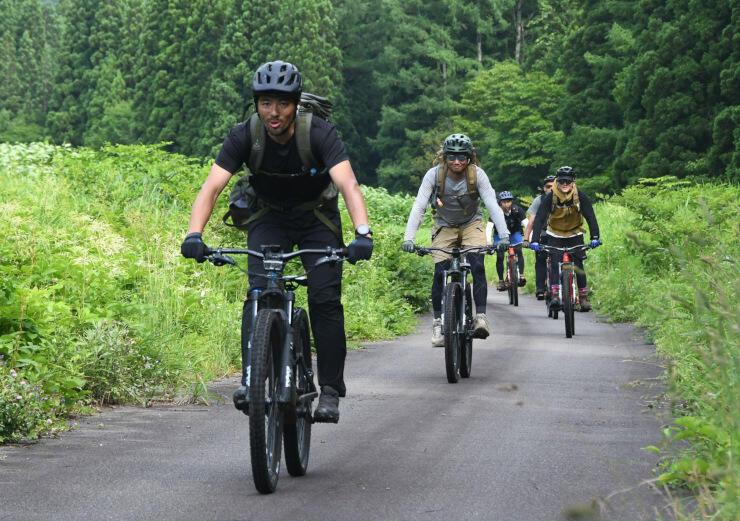 イーバイクに乗って夏場の野沢温泉村を案内する上野さん(左)