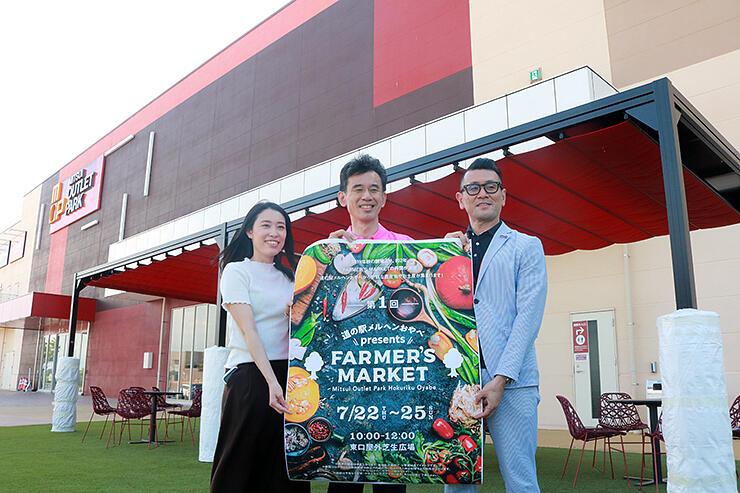 芝生エリアで、ファーマーズマーケットのポスターを手にする島津社長(中央)と熊谷所長(右)
