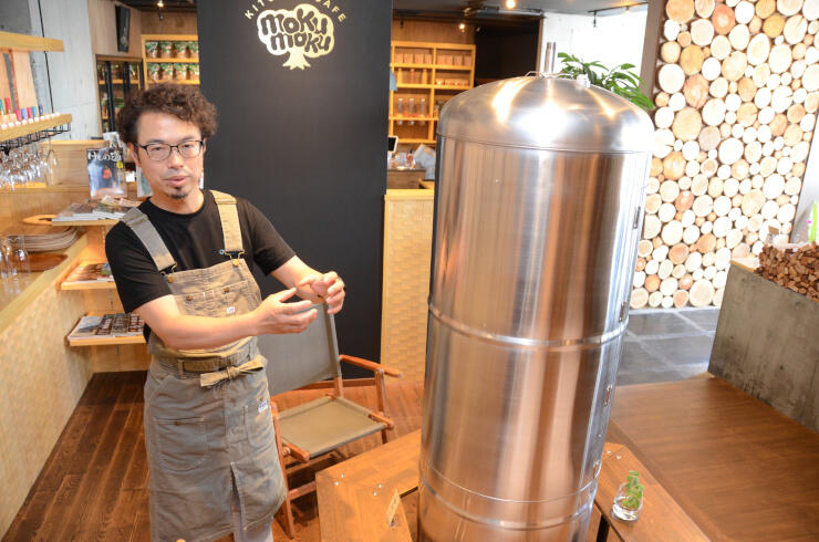 地元産の木材を多用した店内で薫製器を前に今後の構想を語る砂子さん