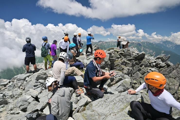 北アルプス槍ケ岳の山頂で360度のパノラマを楽しむ登山者たち=22日午前11時29分