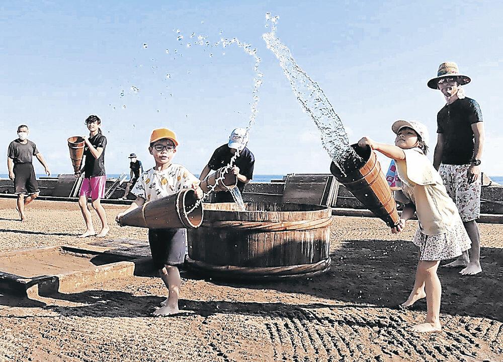 海水を塩田にまく児童=珠洲市清水町の道の駅すず塩田村