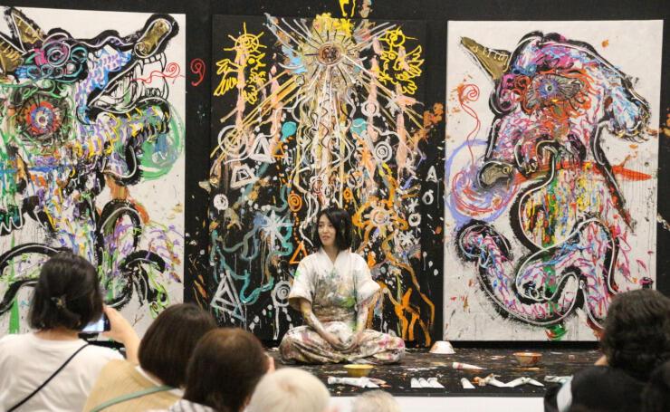 即興で描き上げた作品の前に座る小松さん