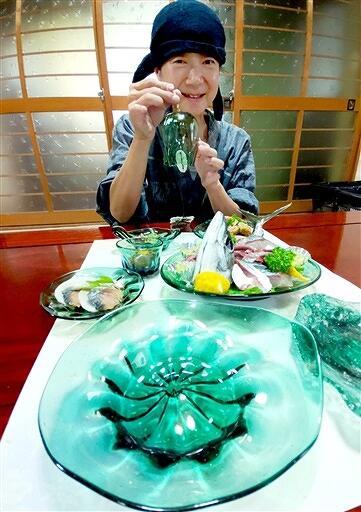 小浜の海の色を表現したガラス作品と竹田さん=7月26日、福井県小浜市田烏の民宿佐助