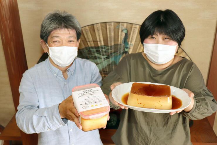 人気の巨大プリンを持つ横渡眞彦さん(左)とあずささん。プリンは1人で平らげる人もいるという=阿賀野市笹岡
