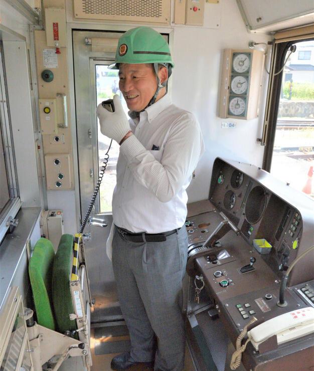 運転室で車内放送を再現する上田電鉄社員