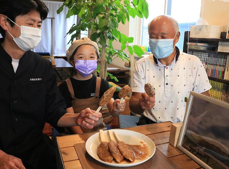 「ヤギの杜ごへいもち」を紹介する(左から)窪田社長、松原さん、金森さん=魚津市六郎丸