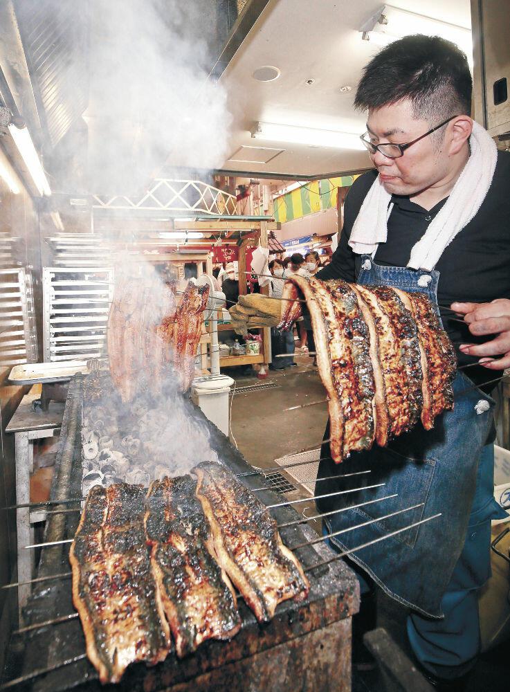炭火でウナギを焼く従業員=金沢市の近江町市場