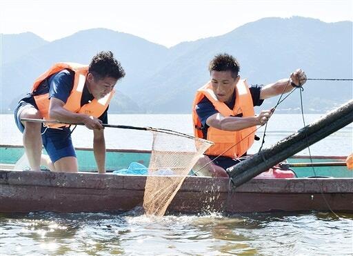 伝統のウナギ筒漁に挑戦する福井ユナイテッドの岩田選手(右)と畠中選手=福井県若狭町鳥浜の三方湖