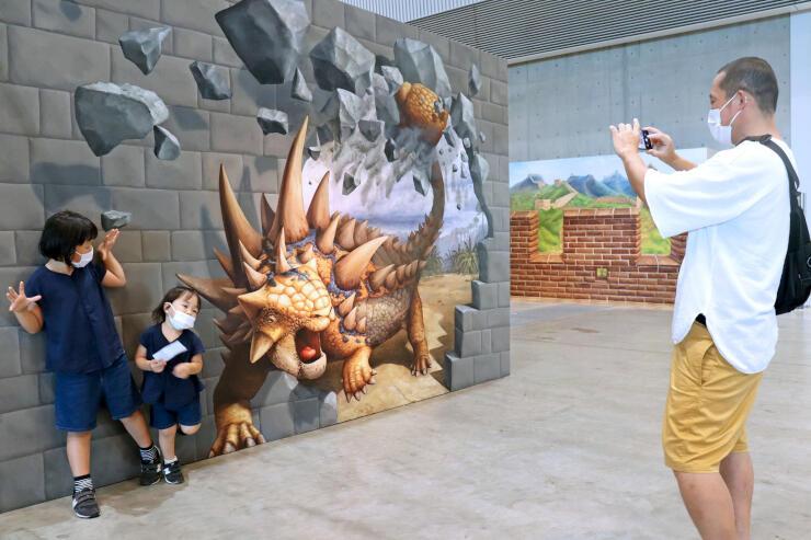 壁から飛び出す恐竜と一緒にポーズを取る子どもたち=28日、新潟市中央区