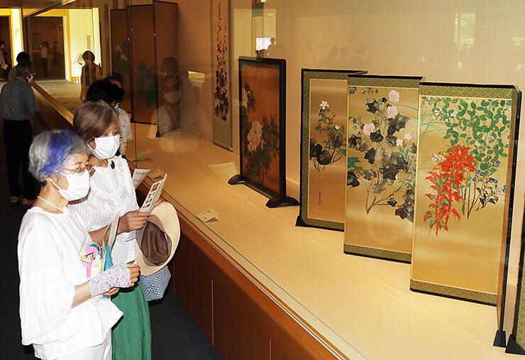 四季の草花を描いた雪佳の屏風に見入る来場者=県水墨美術館