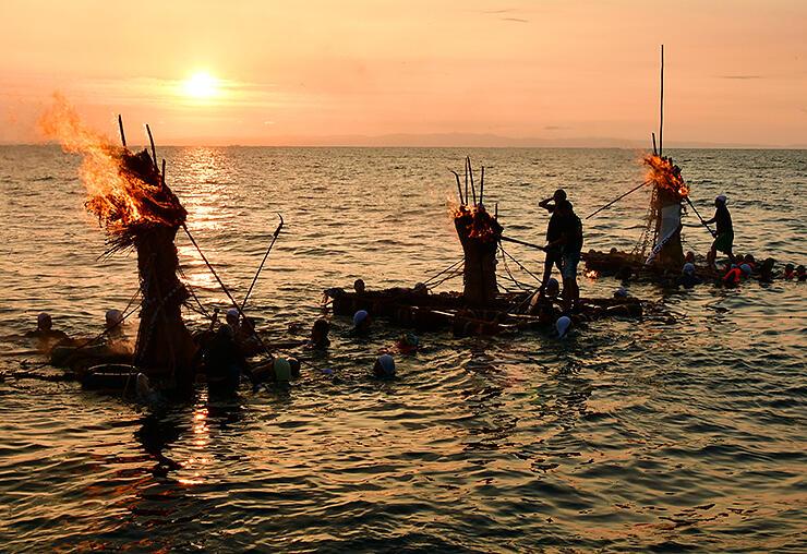 夕日が沈む中、燃えるネブタ=滑川市中川原海岸