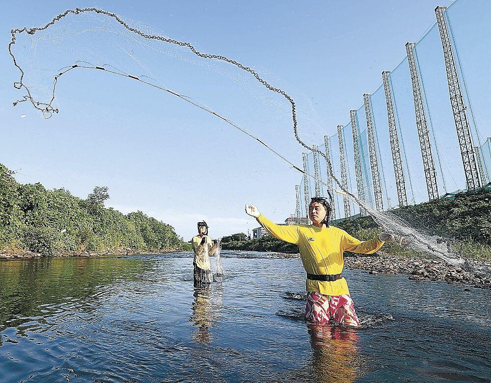 アユをめがけて網を投げる愛好者=金沢市大桑町の犀川