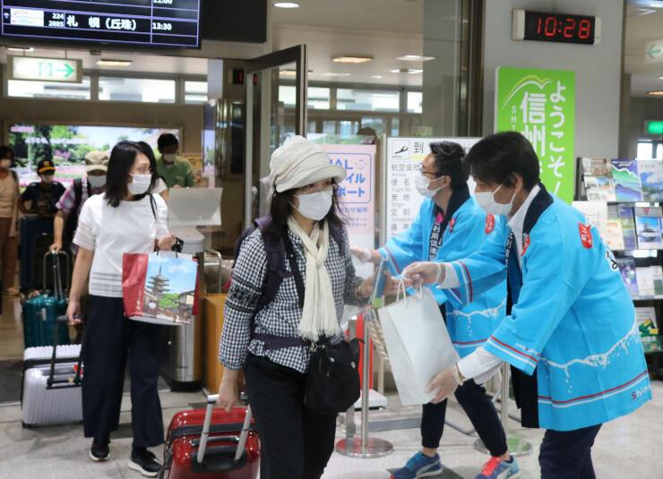 大阪から到着した乗客に観光パンフレットなどを手渡す利用促進協議会のメンバー