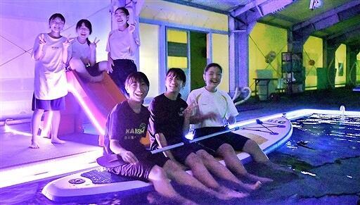 ナイトプール風に電飾が飾られたプールと企画した中学生=福井県大野市B&G海洋センター