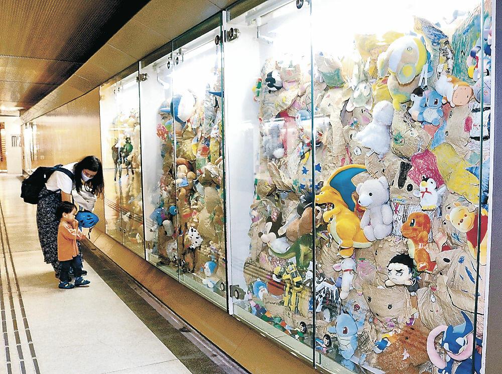 縫いぐるみを集めた展示を眺める通行人=金沢市武蔵町