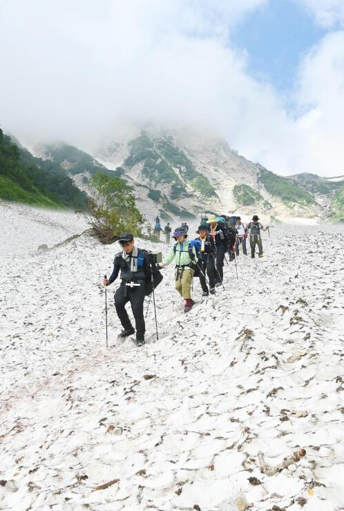 冷たい風が吹き下ろす大雪渓を歩く登山者たち