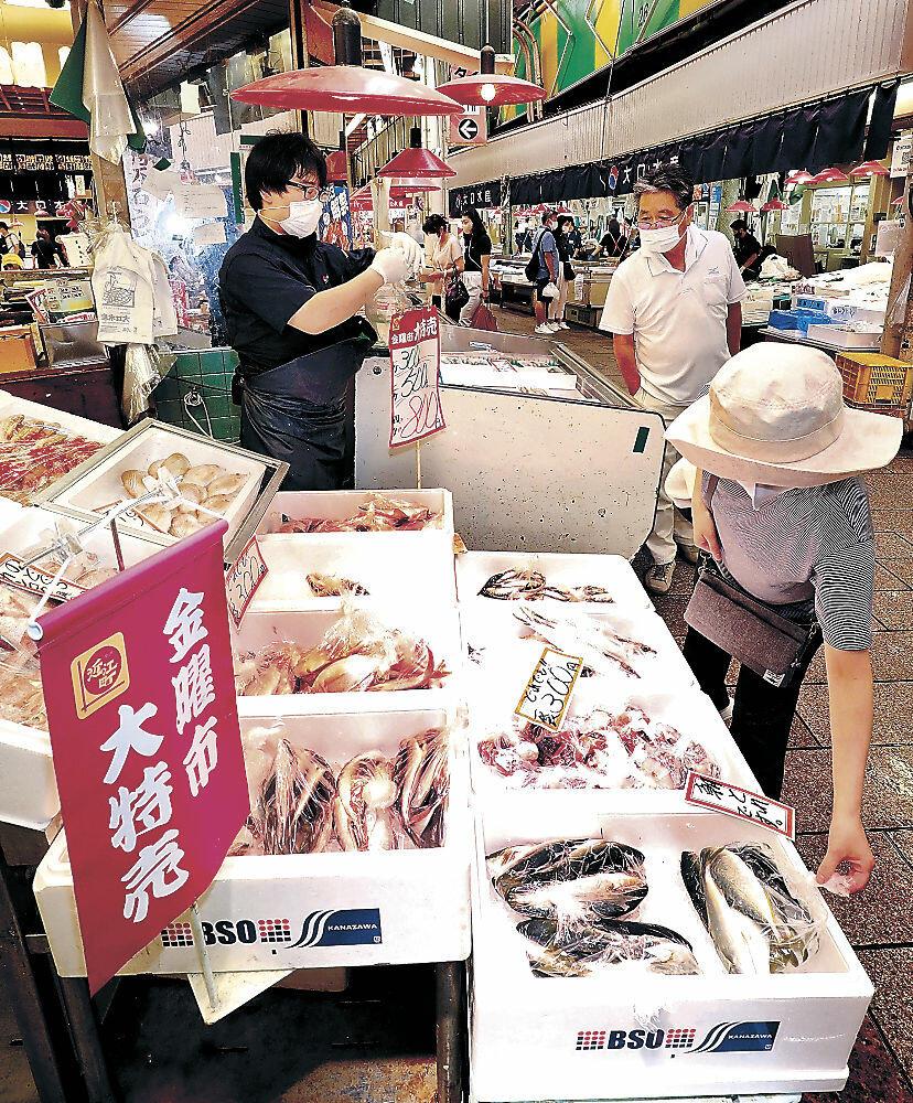 「金曜市」に並んだ特売の魚を品定めする地元客=金沢市の近江町市場の鮮魚店