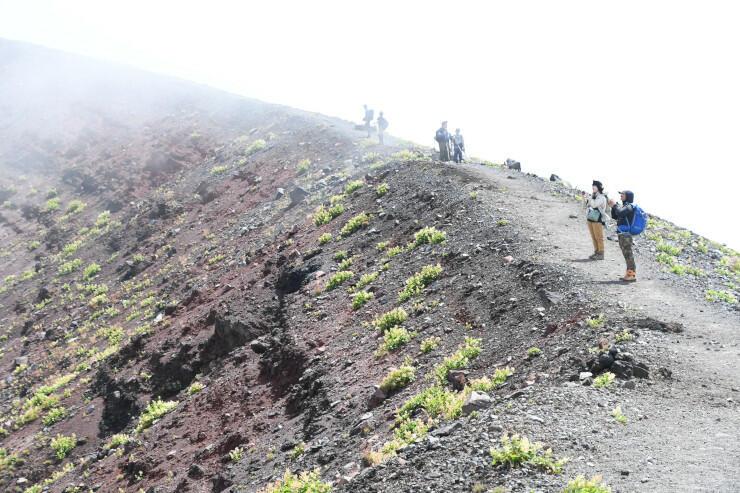 時折雲が晴れると、登山者がカメラで景色を撮影していた=前掛山の山頂付近