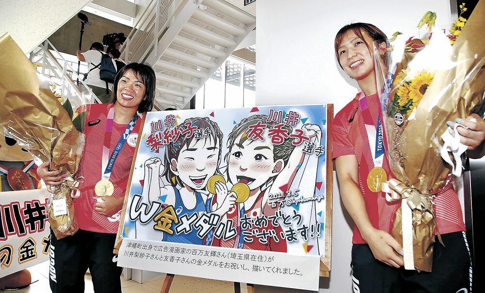 似顔絵のイラストと一緒に記念撮影する川井梨紗子選手(左)と友香子選手=津幡町役場
