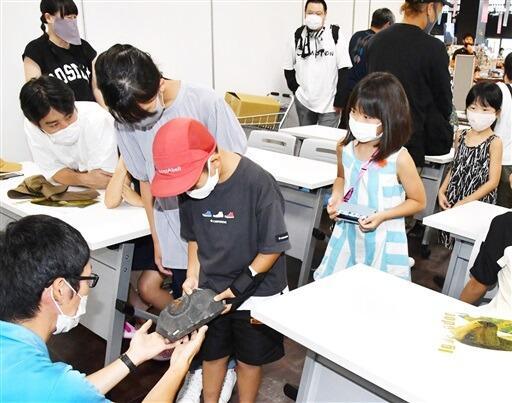 化石教室でアンモナイト化石に触る子どもたち=8月11日、福井県大野市の道の駅「越前おおの 荒島の郷」