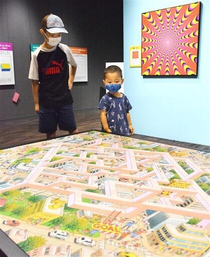 目の錯覚をテーマにした展示に興味津々の子ども=8月11日、福井県福井市自然史博物館分館セーレンプラネット