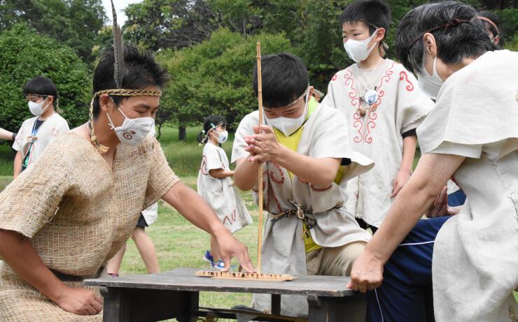 縄文人の格好をして火をおこす県諏訪養護学校の生徒=12日午前10時15分、富士見町の井戸尻史跡公園
