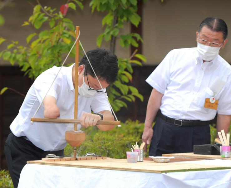 舞錐を使って火をおこす山崎さん(左)=12日午前10時14分、上田市下武石