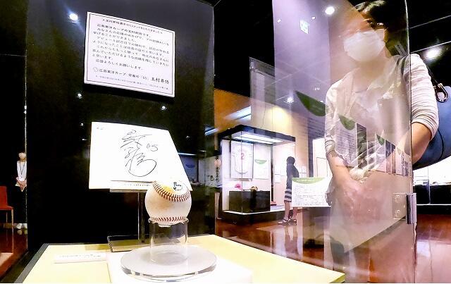玉村昇悟投手の初勝利時のウイニングボールと直筆のサイン色紙=8月13日、福井市の福井県立歴史博物館