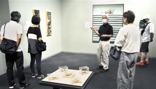 アートディレクターの芹川さん(右から3人目)から作品の説明を受ける参加者=8月14日、福井県小浜市の県立若狭歴史博物館