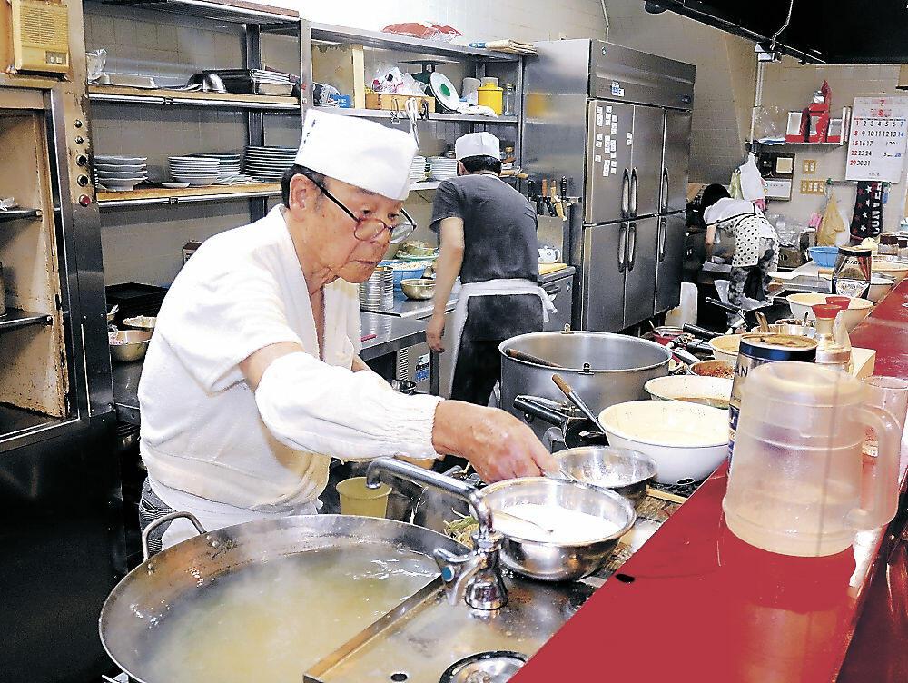 厨房で腕を振るう高輪さん=小松市土居原町