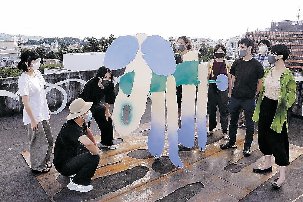 鉄板で犬をかたどった作品を眺めるアーティスト=金沢市広坂1丁目の箔一ビル屋上