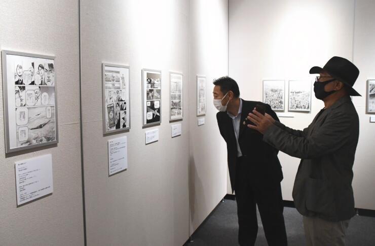漫画「BEGIN」の原画の複製を前に話す武論尊さん(右)