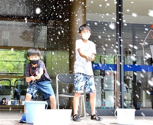 昔ながらの水鉄砲を体験する子ども=8月22日、福井県福井市の県立歴史博物館
