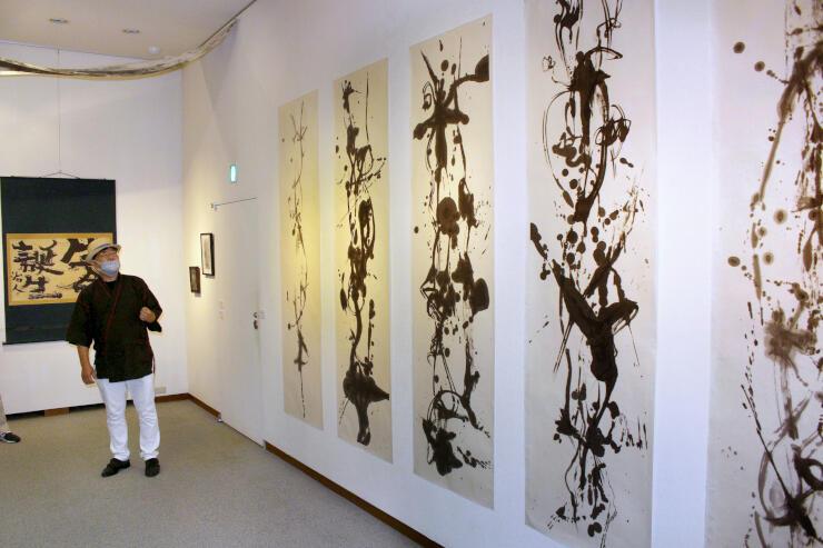 墨で描いたダイナミックな線など展示作を解説する書芸家、平野壮弦さん=十日町市稲葉の「星と森の詩美術館」