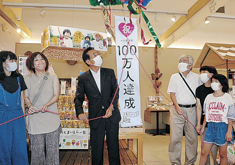 桶谷さん一家とともにくす玉を割る岸市長=羽咋市の道の駅のと千里浜