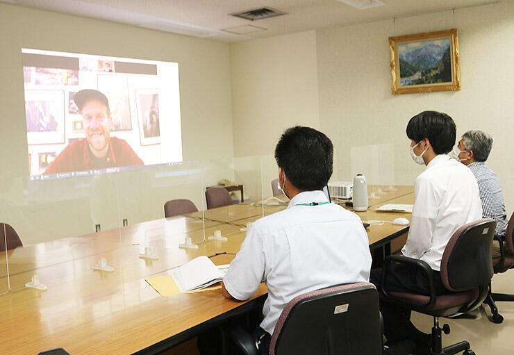 男性の育児をテーマにした写真についてテレビ会議システムで町関係者に語るベーヴマンさん(左)