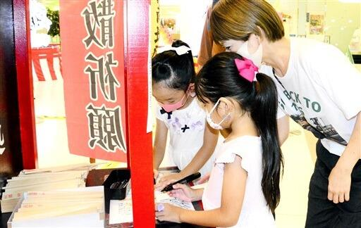祈願木に願い事を書く親子=8月23日、福井県福井市のベル