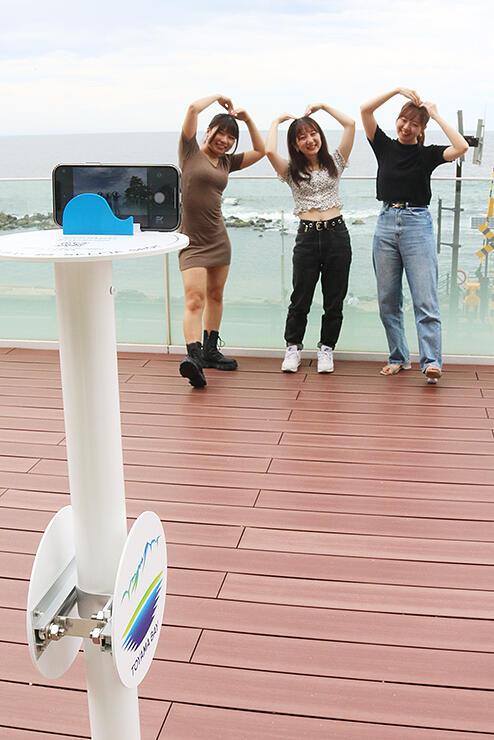 富山湾をバックに自撮りを楽しむ若者