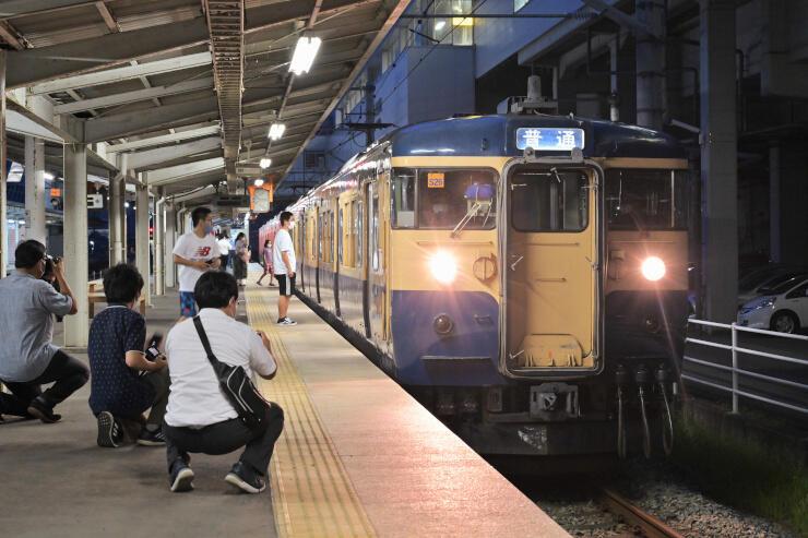 「スカ色」の115系を写真に収める鉄道ファンら=27日午後6時46分、上田駅